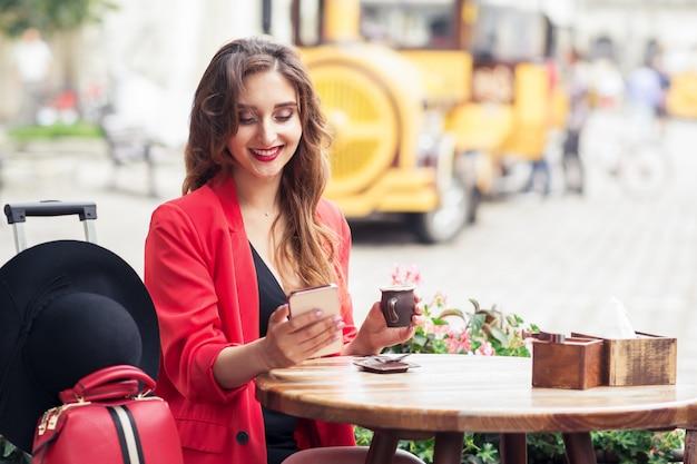 Fille souriante de voyageur est assis café tout en regardant sur le smartphone.