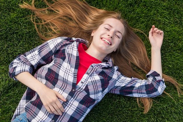 Fille souriante vue de dessus restant sur l'herbe