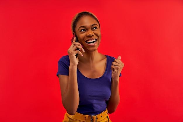Fille avec le sourire dans un t-shirt bleu dans une jupe jaune avec des anneaux d'oreille avec smartphone à la main