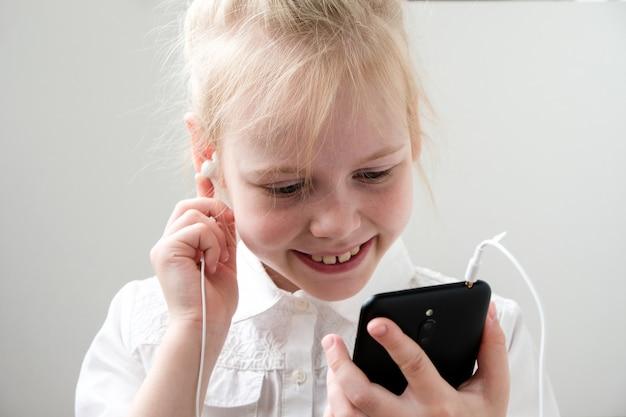 Fille avec un sourire tient un téléphone et des écouteurs dans ses mains