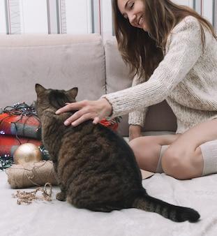 Fille sourit et caresse le chat, décorations de noël autour