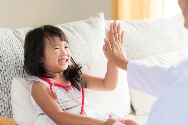 Une fille sourit et donne cinq dollars au médecin. concept de médecine et de soins de santé.