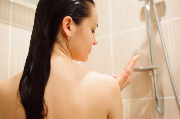 Fille sous la douche dans la cabine de cabine de douche