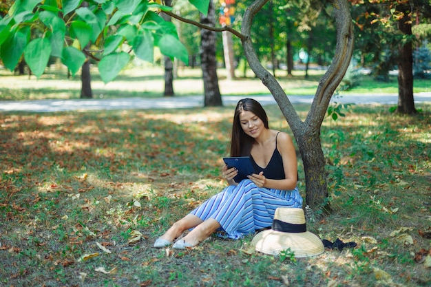 Une fille sous un platane tient un tablet pc dans sa main et le regarde avec surprise, ouvrant joyeusement la bouche, levant la paume au-dessus de l'écran d'émotions
