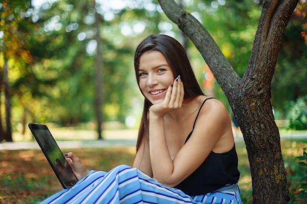 Une fille sous un platane tient un tablet pc dans sa main et le regarde avec surprise