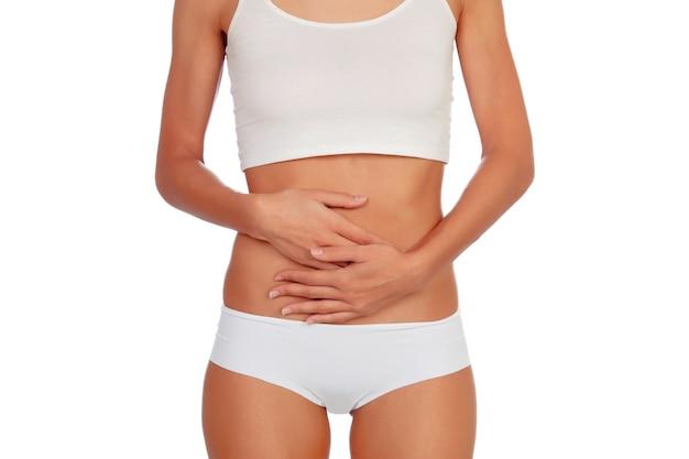 Fille en sous-vêtements blancs avec ses mains sur son ventre