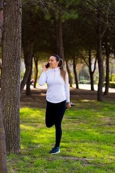 Fille de sport blonde parle sur son téléphone portable et s'étire après l'entraînement. concept sportif