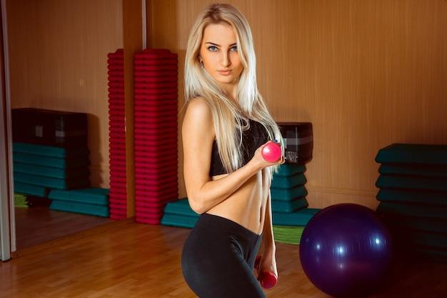 Fille de sport blonde sexuelle avec des haltères dans ses mains en regardant la caméra dans la salle de gym