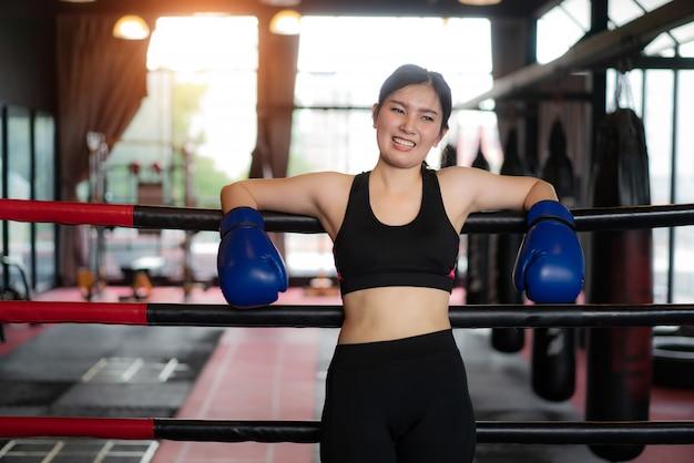 Fille de sport boxeur asiatique fatigué s'appuya sur des cordes rouges noires sur le ring de boxe et se repose après un entraînement dur dans une salle de sport loft noir. ajustement sportif pour un mode de vie sain modèle asiatique du concept de gym de boxe.