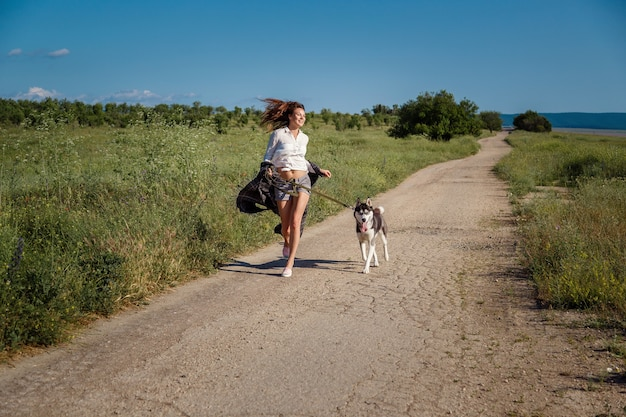 Fille de sport court avec un chien le husky sibérien sur la route