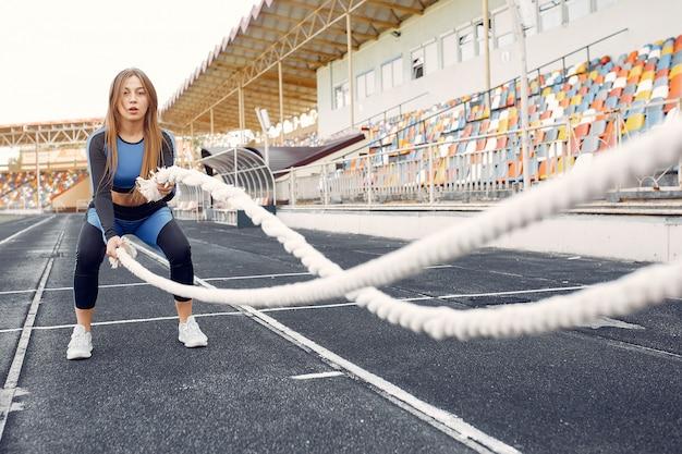 Fille de sport dans une formation uniforme bleu au stade avec une corde