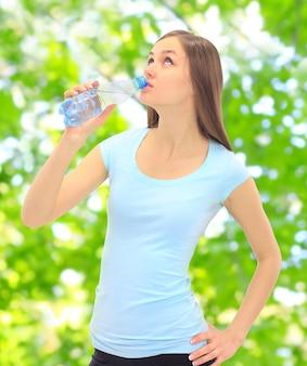 Fille de sport eau potable dans la rue.
