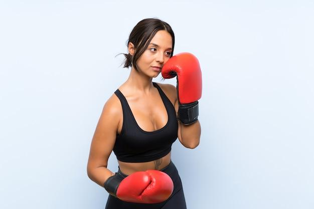 Fille de sport jeune avec des gants de boxe sur fond bleu isolé