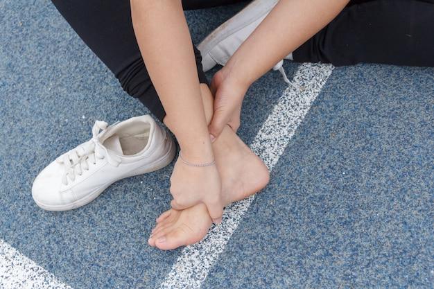 Fille de sport tenant la cheville dans la douleur due à une entorse à la cheville. blessure due au concept d'entraînement