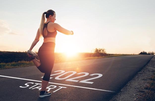 Fille sportive attendant sur la ligne de départ pour commencer la nouvelle année 2022 nouveaux objectifs, plans et visions