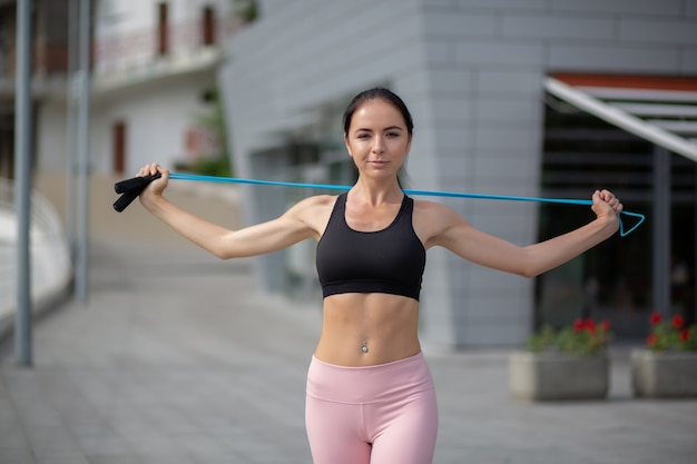 Fille sportive attirante faisant l'entraînement de mains avec la corde à sauter