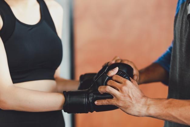 Fille sportive belle femme avec les gants de boxe en arrière au gymnase