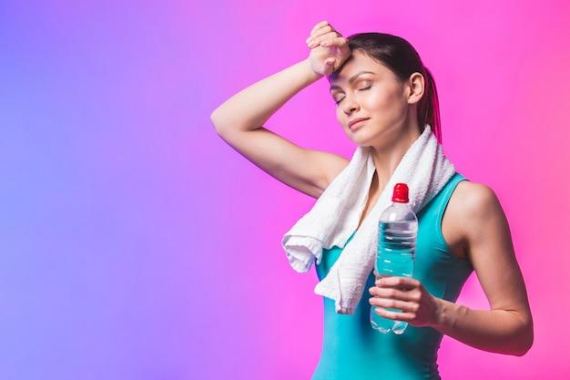 Fille sportive avec une bouteille d'eau et une serviette sur ses épaules. photo du modèle de fitness isolé sur fond blanc.