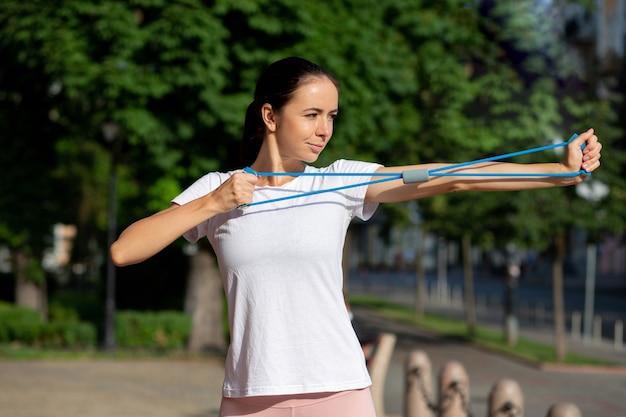 Fille sportive brune faisant son entraînement avec une bande de résistance bleue dans le parc