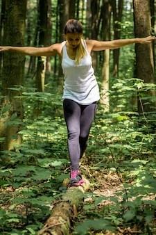 Fille sportive dans les bois sur le chemin, échauffement avant le jogging, le sport