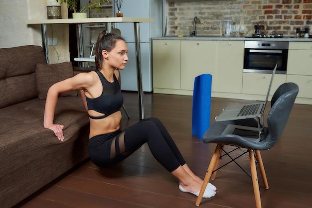 Une fille sportive dans un costume moulant noir fait des exercices de triceps et de poitrine et regarde une vidéo d'entraînement en ligne sur un ordinateur portable. une entraîneure dirige un cours de fitness à distance à la maison.