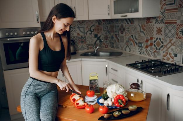 Fille sportive dans une cuisine avec des légumes