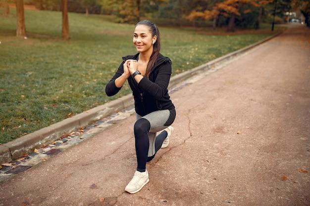 Fille sportive dans une formation en haut noir dans un parc en automne