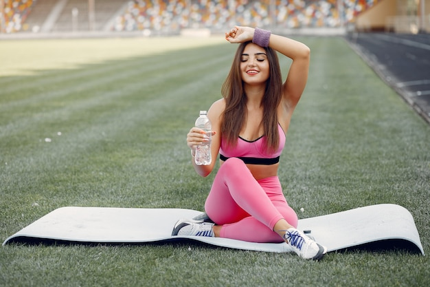 Fille sportive dans une formation uniforme rose au stade
