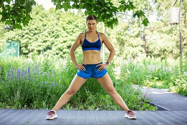 Une fille sportive dans un survêtement bleu s'entraîne dans le parc se tient dans une pose avec les jambes écartées