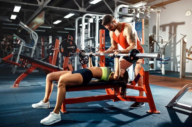 Fille sportive faisant des exercices de poids avec l'aide de son entraîneur personnel au gymnase.