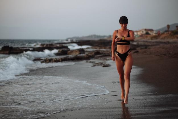 Une fille sportive en maillot de bain noir se promène au bord de la mer au coucher du soleil