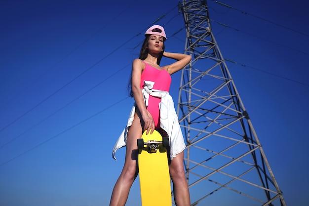 Fille sportive en maillot de bain rose tient son longboard jaune