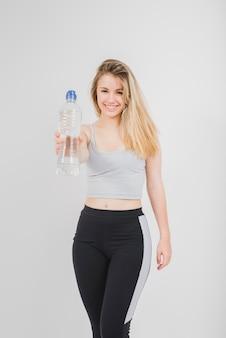 Fille sportive montrant une bouteille d'eau