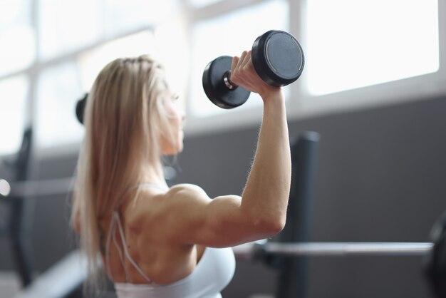 Fille sportive montrant des exercices de force physique du corps bien entraînés pour les biceps