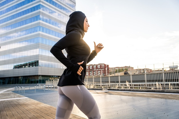 Fille sportive musulmane avec entraînement du corps en forme à l'extérieur