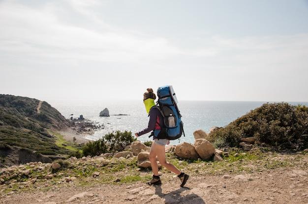 Fille sportive qui marche avec un sac à dos de randonnée et colle un masque spécial contre la poussière