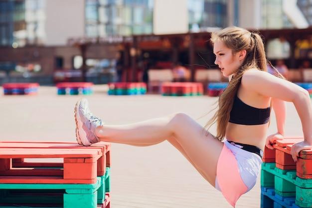Fille sportive de remise en forme portant des vêtements de sport de mode sur le mur de la rue, sports de plein air, style urbain. modèle adolescent, dans, swag, vêtements, poser, dehors