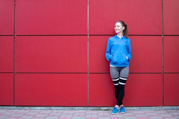 Fille sportive se dresse contre un mur rouge en tenue de sport
