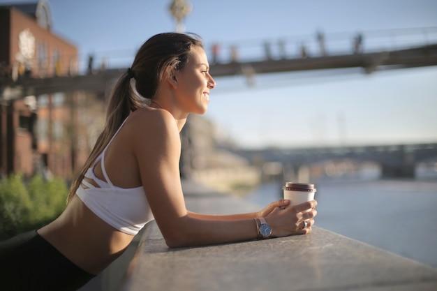 Fille sportive se reposer boire un café et regarder la vue