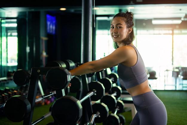 Fille sportive, soulever des poids dans la salle de gym