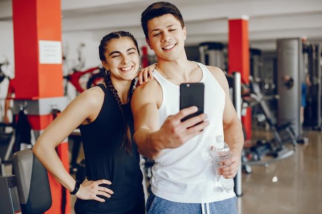 Une fille de sportswear belle et athlétique s'entraînant dans la salle de gym avec son petit ami