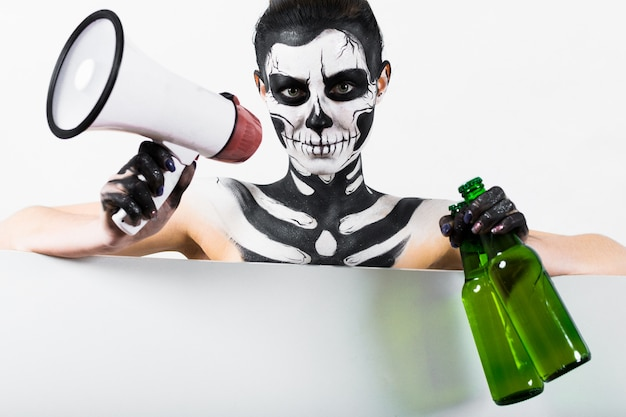 Fille avec squelette maquillage tenir la bouteille et le mégaphone