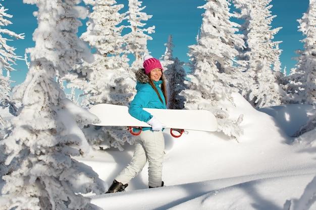 Fille avec station de ski d'hiver snowboard