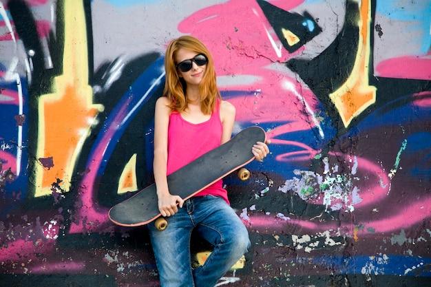 Fille de style avec planche à roulettes près du mur de graffitis.