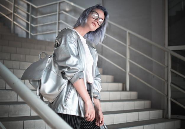 Une fille de style spatial aux cheveux bleus cendrés est vêtue d'une cape avec un tissu argenté et un sac à dos sur les épaules posant dans la rue avec des lunettes à l'arrière-plan des étapes du don.