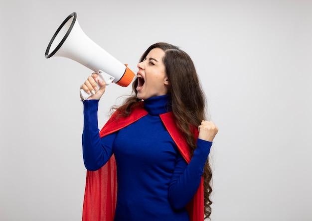Fille de super-héros caucasien agacé avec cape rouge garde le poing et crie dans le haut-parleur à côté isolé sur mur blanc avec espace de copie