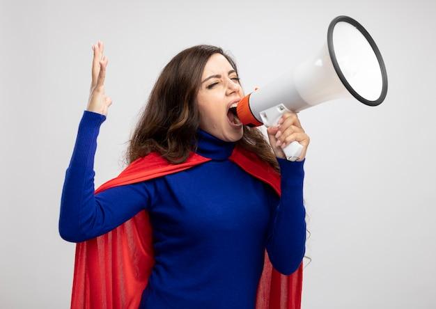 Fille de super-héros caucasien agacé avec cape rouge se dresse avec la main levée et crie dans haut-parleur isolé sur mur blanc avec espace copie