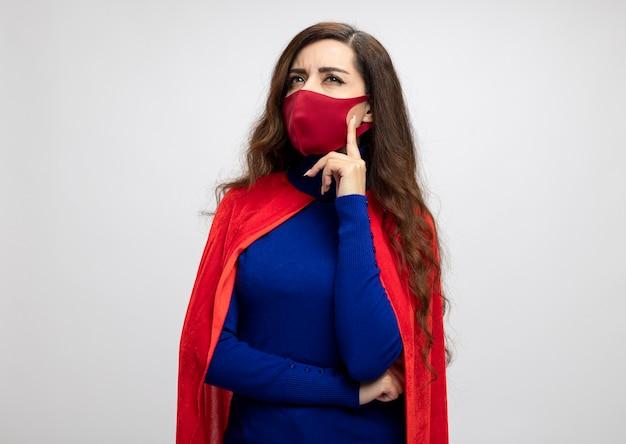 Fille de super-héros caucasien réfléchie avec cape rouge portant un masque de protection rouge met la main sur le menton à côté isolé sur mur blanc avec espace copie