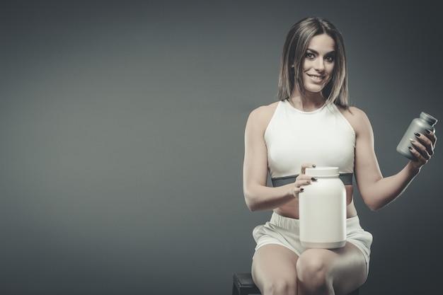 Fille avec supplément poudre de secousse de protéine de lactosérum