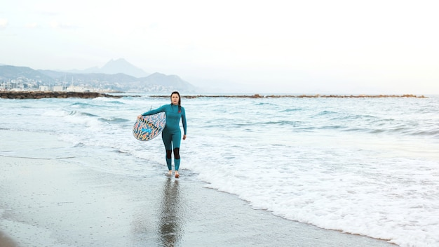 Fille de surfeur marchant avec planche sur la plage de sable. surfeuse femme. belle jeune femme à la plage. sports nautiques. mode de vie sain et actif. vacances d'été. sport extrême.